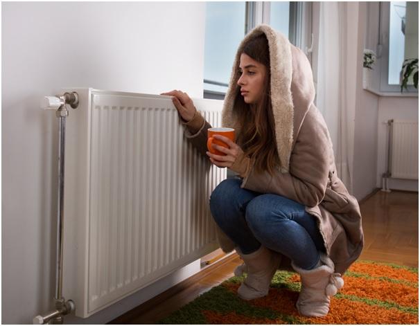 Chica con frío arrimada a un radiador