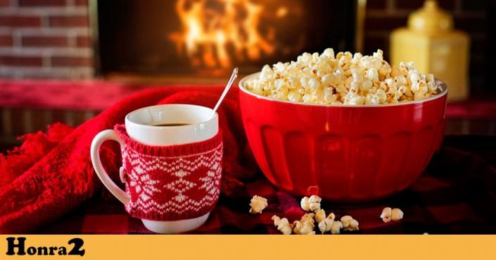 Taza con café caliente y bol de palomitas con chimenea encendida al fondo