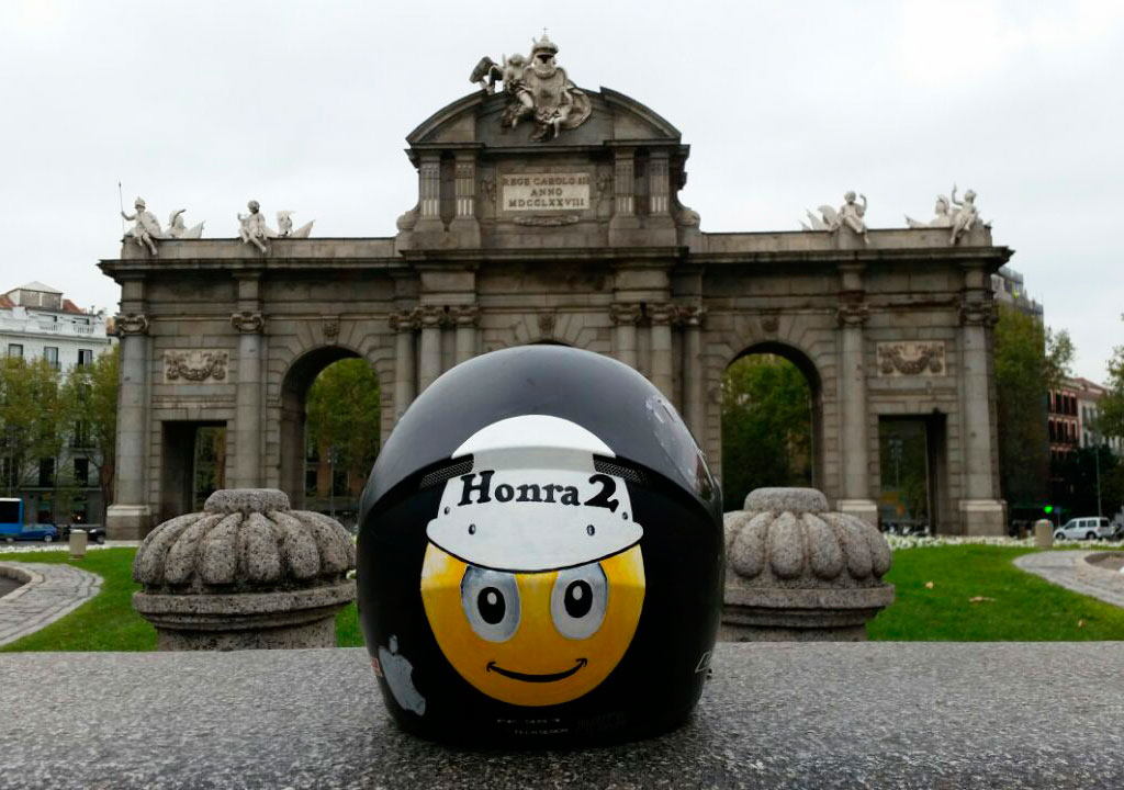 Casco de moto con pegatina de Honra2 y la Puerta de Alcalá en segundo plano