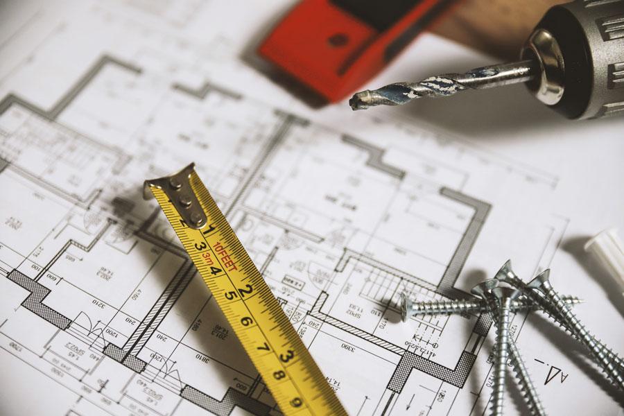Imagen de unos planos de una casa con un metro, unos clavos y un taladro encima